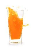 Färgstänk i exponeringsglas av orange fruktsaft med flyg tappar Arkivbild