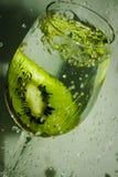 Färgstänk och stycke av frukt i exponeringsglaset av vatten Arkivfoto