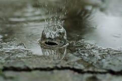 Färgstänk regn på asfalt droppar arkivfoto