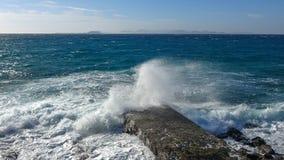 Färgstänket av vågorna på den steniga kusten Arkivfoto