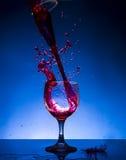 Färgstänkexponeringsglasrött vin fotografering för bildbyråer