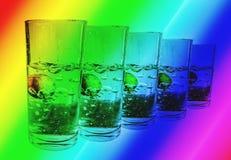 Färgstänkvatten i fem exponeringsglas på regnbågebakgrund Royaltyfri Fotografi