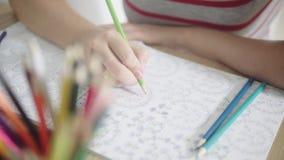 Färgvideo av en kvinnahand som rymmer en blyertspenna och färgar en vuxen färgläggningbok Aktivitet för att koppla av och koncent stock video