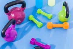 Färgvikter, hantlar, Kettlebells och isotonic drinkar på idrottshallen Inomhus foto royaltyfria foton