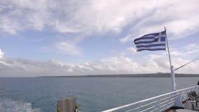 Färja i den Grekland sikten på havet och den vinkande nationsflaggan lager videofilmer