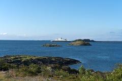 Färja på en ojämn stenig kustlinje Arkivbild