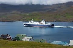 Färja som kryssar omkring in i en fjord av Faroe Island Arkivbilder