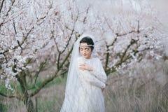 Fästmön är i en vårblomningträdgård arkivfoton