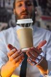 Få att sväva en kopp kaffe på gömma i handflatan av en person royaltyfri bild