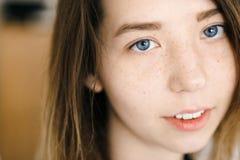 Få fräknar ståenden av den unga gulliga flickan med blåa ögon Arkivfoto
