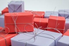 Få gåvor som slås in i rött och lila papper royaltyfri foto