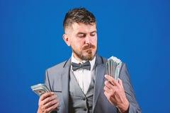 Få kassa lätt och snabbt Affär för kassatransaktion För dräkthåll för man formell hög av blå bakgrund för dollarsedlar royaltyfria bilder