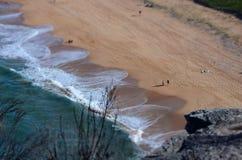 Få människor på stranden Arkivfoto