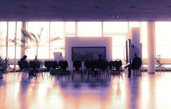 Få människor som sitter på stolar i väntande på seminarium för modern salong för att börja Arkivfoton