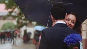 Få skott av härligt barn kopplar ihop under paraplyet, är den attraktiva flickan krama och kyssande hennes pojkvän flicka stock video