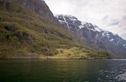 få små lantliga hus i aurlandsfjord i försommar Royaltyfri Bild