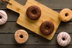 Få sorter av donuts på den svarta bakgrunden Fotografering för Bildbyråer