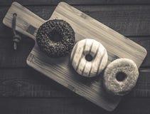 Få sorter av donuts på en grå träbakgrund Fotografering för Bildbyråer