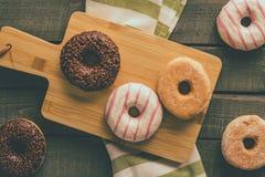 Få sorter av donuts på träbakgrunden Arkivfoton