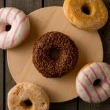 Få sorter av donuts på träbakgrunden Arkivfoto