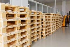 Få tomma träpaletter för lagring i ett tomt lager royaltyfri fotografi