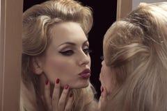 Fåfäng flicka framme av spegeln Arkivbilder