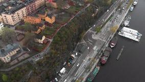 fågelöga för flyg- sikt 4k av vägen med trafik i mitt mellan floden och husen stock video