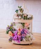 Fågelbur med kulöra blommor royaltyfri fotografi