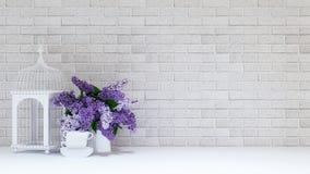 Fågelburen med vasen av lilor blommar och kuper på tegelstenbakgrund Royaltyfri Bild