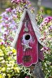 Fågelhus i blommaträdgård Royaltyfri Foto