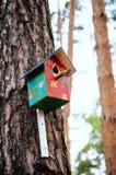 Fågelhus som hänger på en trädstam royaltyfri foto