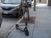 Fågeln trans. startar upp, elektrisk scouter som parkeras på sidewa fotografering för bildbyråer