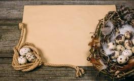 Fågelrede med ägg från en sida och spole av rep med vaktelägg i andra sidan av arket av papper för text på lantlig wood backgro arkivbilder