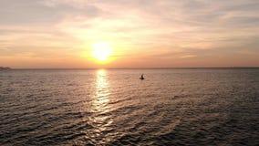 Fågels sikt för öga av fartyget som korsar stillhetvattenyttersida av havet under purpurfärgad aftonsolnedgång på horisonten, här lager videofilmer