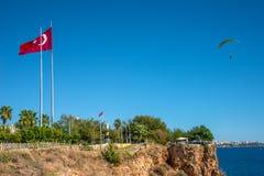 Fågelsikt av Antalya och medelhavs- seacoast och strand med en paraglider och en turkisk flagga, Antalya, Turkiet royaltyfri foto