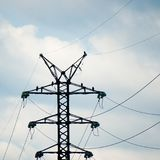 Fåglar av svarta drakar för rovet som sitter på rostade metallstrålar av en kraftledning, står högt mot den molniga himlen Royaltyfria Bilder