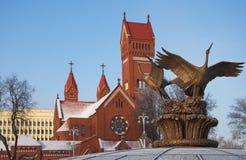 Fåglar mot den röda kyrkan Arkivfoto