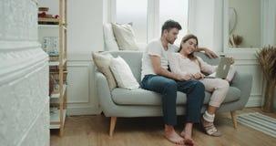 Fånga har ett par i morgonen en trevlig tid tillsammans i vardagsrum med hemtrevlig stil, dem ser igenom arkivfilmer