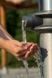 Fånga nytt och kallt vatten med händer Arkivbild