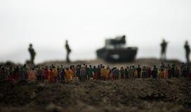 Fångat av fientligt begrepp Militära konturer och folkmassa på bakgrund för krigdimmahimmel Soldater och pansarbilar för världskr arkivfoto