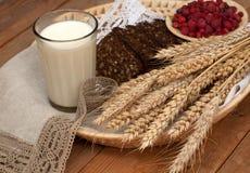 Fånget av öron, nytt bröd, hallon och ett exponeringsglas av mjölkar på ett sugrörmagasin med en linneservett Royaltyfria Bilder