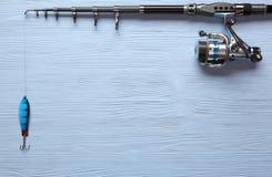 Fångstredskapet - fiskesnurr, hakar och lockar på träbac Arkivbild