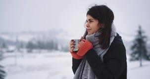 Får att bära för ung dam för detaljcloseup varm kläder och att stå i överkant av berget varma dricker någon varm drink från lager videofilmer