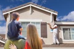 Får det hållande ögonen på huset för den unga familjen målat av målaren arkivbilder