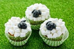 Fårmuffin, lammmuffin, förtjusande påskmuffin som dekoreras med den vita marshmallowen, och svart fondant arkivfoto