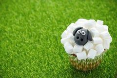 Fårmuffin, lammmuffin, förtjusande påskmuffin som dekoreras med den vita marshmallowen, och svart fondant arkivbilder