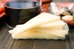 Fårost i delar och exponeringsglas av vin på trä Royaltyfria Bilder