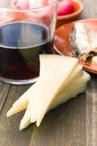 Fårost i delar och exponeringsglas av vin på trä Royaltyfria Foton