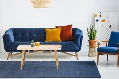 Fåtölj bredvid den blåa soffan med kuddar och trätabellen i plan inre med växten Verkligt foto royaltyfri foto