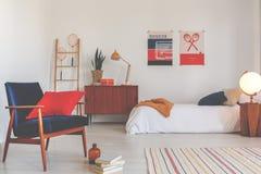 Fåtölj för tappningsammetblått med den röda kudden i det eleganta oldschoolsovrummet, verkligt foto royaltyfri foto